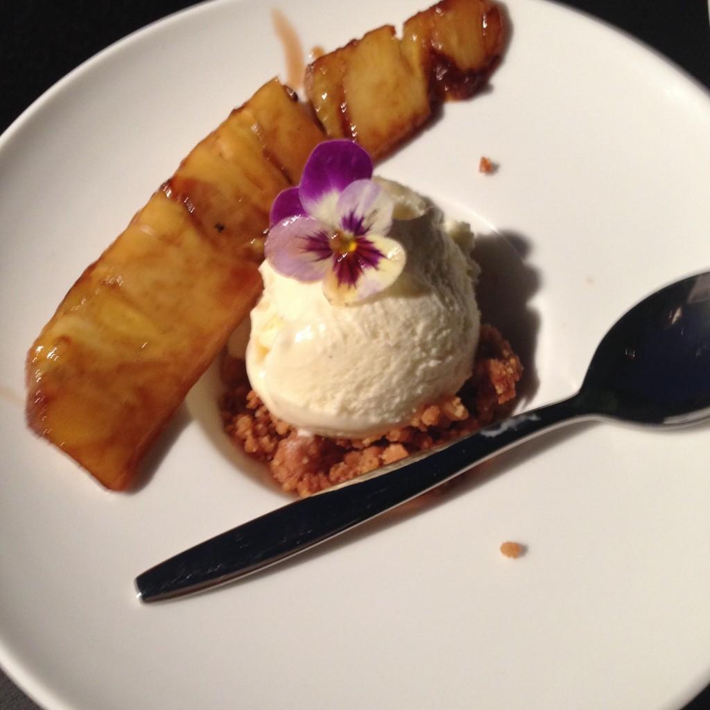 Geroosterde ananas ingestoken met vanille, rode pepers, citroengras en kaneel met rumstroop en vanille ijs